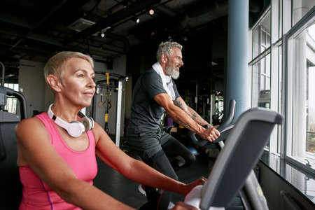 Mature couple working out on gym cycles Standard-Bild