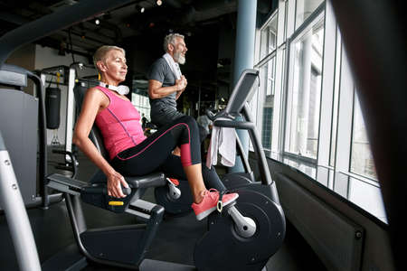 Determined senior couple working out on excercise bikes.