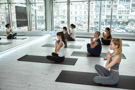 Active diverse women practice yoga in fitness club Standard-Bild