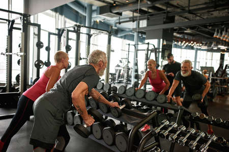 Cheerful strong man excercising together with fit wife