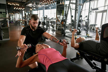Gym trainer supporting mature woman while working out Standard-Bild