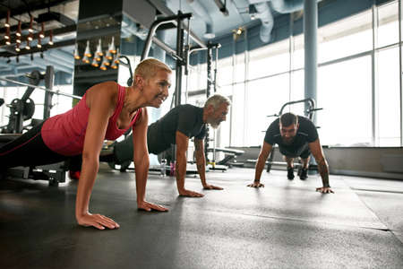 Happy sportswoman standing in plank next to two men