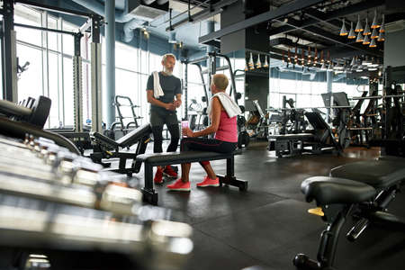 Healthy lifestyle after retirement, modern gym with couple of senior people after working out Standard-Bild