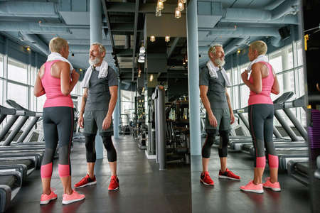 Sporty aged woman and man in gym, mirror reflection of senior couple
