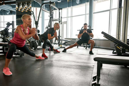 Mature woman and man doing side lunge exercise under trainers supervision Standard-Bild