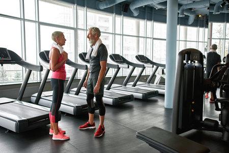 Two happy senior people in fitness center talking near treadmills