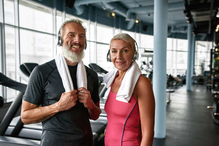 Happy senior couple posing in gym after working out