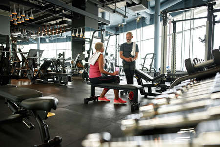Two happy senior people in fitness center talking before training