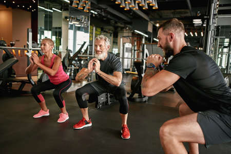 Active elderly woman and man performing squats in gym Standard-Bild