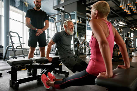 Pair of elderly woman and man working out with trainer