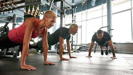Strong senior couple doing plank at gym