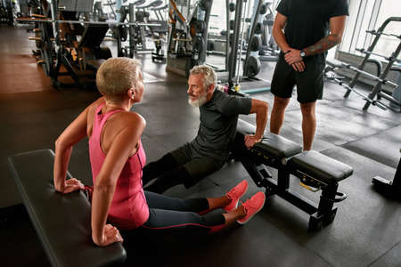 Middle age woman excercising with male friend in gym Standard-Bild