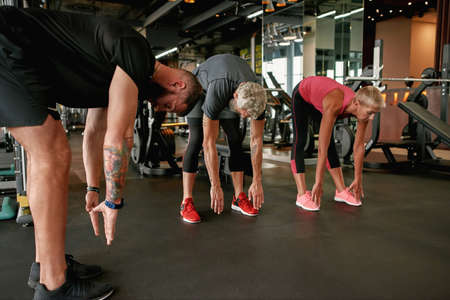 Fitness instructor teaching mature man and woman in gym