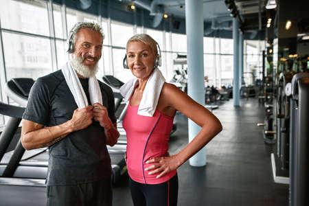 Senior couple with strong bodies and good spirits posing in gym Standard-Bild