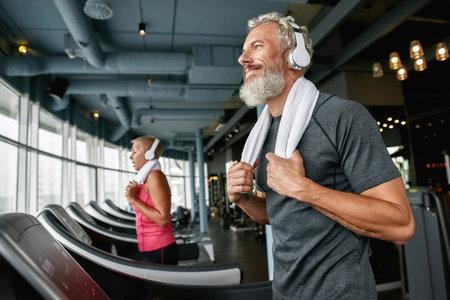 Happy senior man enjoying excercising in gym