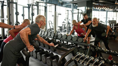 Strong man and woman exercising with dumbbells in gym
