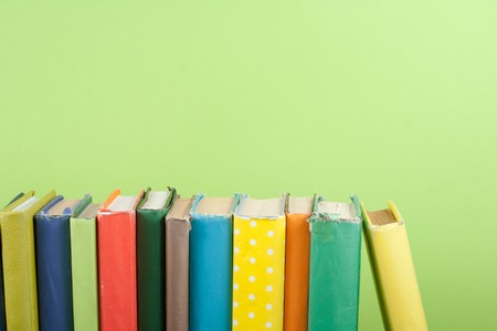 Book stacking. Open hardback books on wooden table and green background. Back to school. Copy space for ad text.