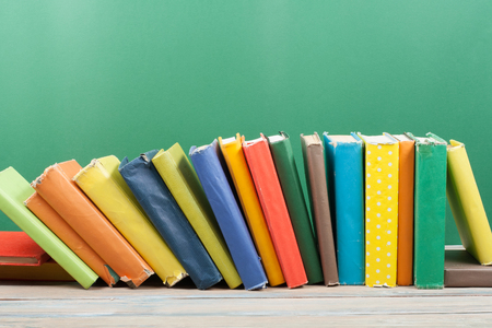 Book stacking. Open hardback books on wooden table and green background. Back to school. Copy space for ad text