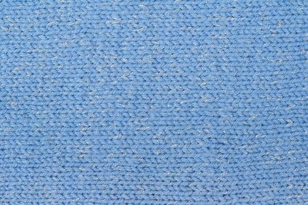 The texture of a knitted woolen fabric blue. Background.