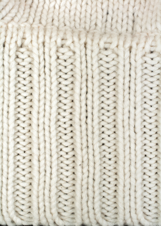 Sweater or scarf fabric texture large knitting. Knitted jersey background with a relief pattern. Braids in knitting . Wool hand- machine, handmade. Stock Photo