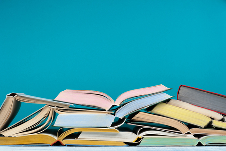 Hardback colorful books on blue background. Back to school. Copy space for text. Education business concept Stock Photo