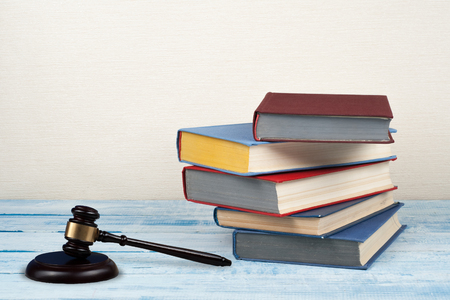 Law concept open book with wooden judges gavel on table in a courtroom or law enforcement office, beige background. Copy space for text. Stock Photo