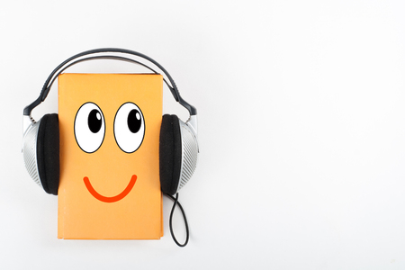 Audiobook on white background. Headphones put over yellow hardback book, empty cover, copy space for ad text. Distance education, e-learning concept.