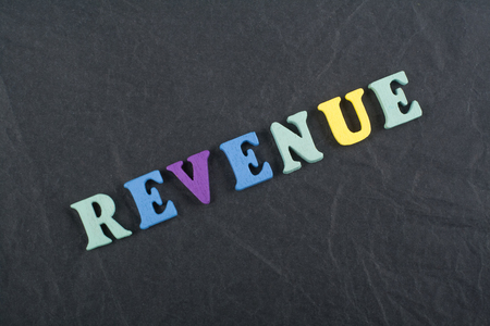 REVENUE word on black board background composed from colorful abc alphabet block wooden letters, copy space for ad text. Learning english concept. Stok Fotoğraf