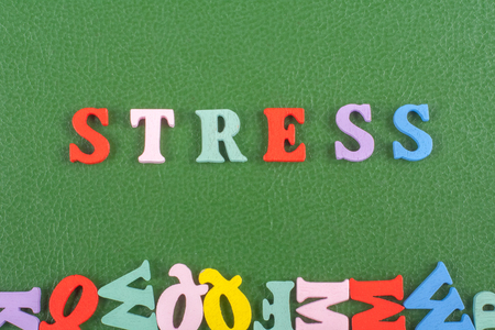 unsolved: STRESS word on green background composed from colorful abc alphabet block wooden letters, copy space for ad text. Learning english concept. Stock Photo