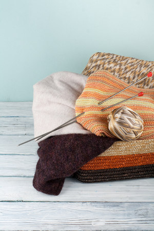 sewing box: Ball of wool, needles and woolen sweater with spokes for handmade knitting in basket on wooden table.