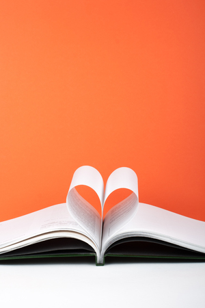 Old open hardback book, page decorate into a heart shape for love in Valentines. love with open book heart. Stok Fotoğraf - 79264500