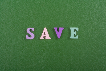 discounting: SAVE word on green background composed from colorful abc alphabet block wooden letters, copy space for ad text. Learning english concept. Stock Photo