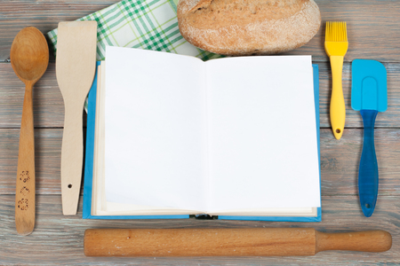 paper pin: Open recipe book on wooden background, spoon, rolling pin , green checkered tablecloth.