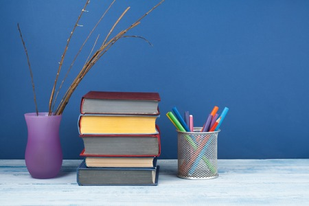 Book stacking. Open book, hardback books on wooden table and blue background. Back to school. Copy space for text.