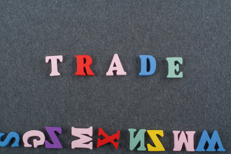 barter system: TRADE word on black board background composed from colorful abc alphabet block wooden letters, copy space for ad text. Learning english concept.