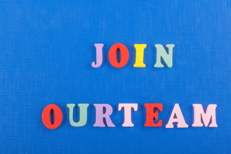 JOIN OUR TEAM word on blue background composed from colorful abc alphabet block wooden letters, copy space for ad text. Learning english concept. Stock Photo