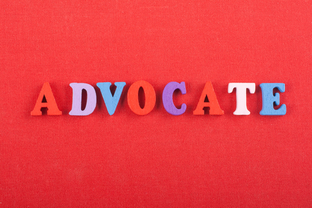ADVOCATE word on red background composed from colorful abc alphabet block wooden letters, copy space for ad text. Learning english concept.