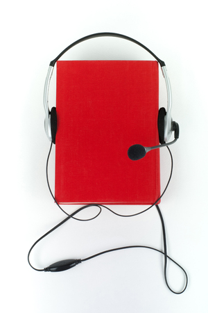 audio book: Audiobook on white background. Headphones put over red hardback book, empty cover, copy space for ad text. Distance education, e-learning concept.