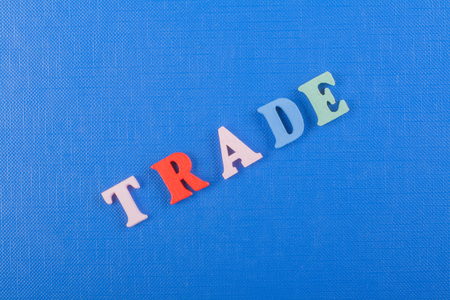 proprietary: TRADE word on blue background composed from colorful abc alphabet block wooden letters, copy space for ad text. Learning english concept.