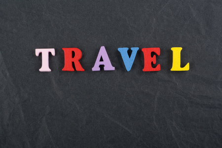 sight seeing: TRAVEL word on black board background composed from colorful abc alphabet block wooden letters, copy space for ad text. Learning english concept. Stock Photo