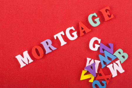 MORTGAGE word on red background composed from colorful abc alphabet block wooden letters, copy space for ad text. Learning english concept. Stock Photo