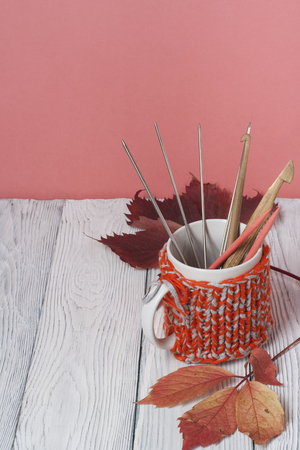 tejido de lana: Todavía del otoño taza de café de la vida en la tabla de madera. Suéter hecho punto con hojas de otoño, radios, ganchillo y taza de café. Fondo de estilo cambiante de otoño. Vista superior