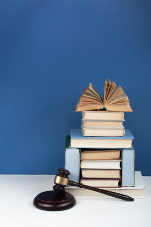 Law concept open book with wooden judges gavel on table in a courtroom or law enforcement office, blue background. Copy space for text.