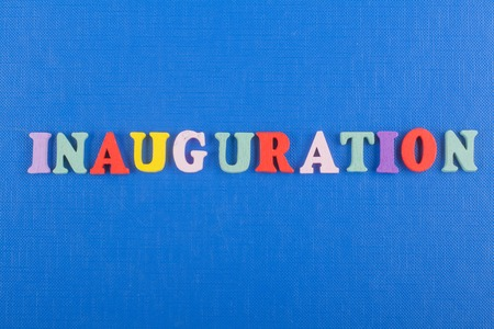 Inauguration . English word on blue background composed from colorful abc alphabet block wooden letters, copy space for ad text. Learning english concept.
