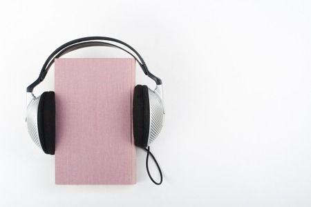 Audiobook on white background. Headphones put over pink hardback book, empty cover, copy space for ad text. Distance education, e-learning concept. Stock Photo