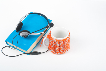 audio book: Audiobook on white background. Headphones put over blue hardback book, empty cover, red cup, copy space for ad text. Distance education, e-learning concept. Stock Photo