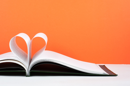 Old open hardback book, page decorate into a heart shape for love in Valentines. love with open book heart. Foto de archivo