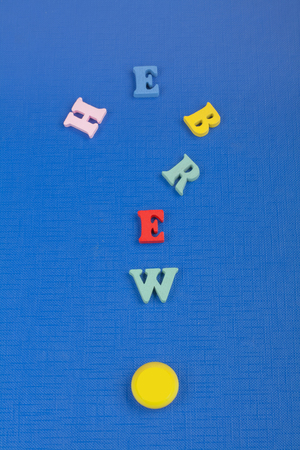 hebrew letters: HEBREW word on blue background composed from colorful abc alphabet block wooden letters, copy space for ad text. Learning english concept. Stock Photo