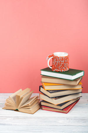 Book stacking. Open book, hardback books on wooden table and pink background. Back to school. Copy space for text.