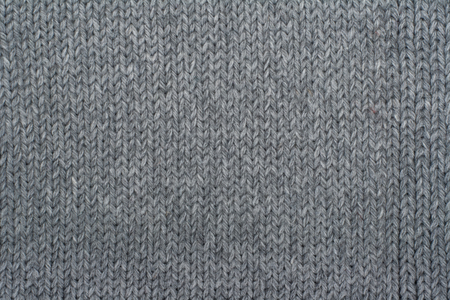 Sweater or scarf fabric texture large knitting. Knitted jersey background with a relief pattern. Wool hand- machine, handmade, gray. Stock Photo
